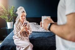 Woman in bathrobe, towel on her head sits on bed, using smartphone. In foreground is man with cup of coffee in his hands stock images