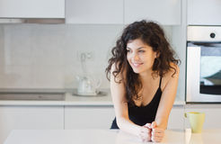 Morning woman in the kitchen. Smiling woman in the morning having coffee or tea in the kitchen Royalty Free Stock Photos
