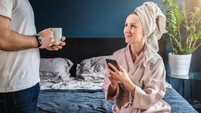 Woman in bathrobe and towel on head sitting on bed, holding smartphone, talking to standing next to her husband. stock image