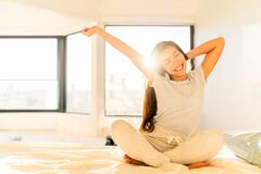 Free Morning Woman Waking Up Stretching In Bed In Sunshine Sunrise Early Bird Happy Asian Girl. Healthy Routine Home Royalty Free Stock Photo - 207875155