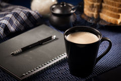 Morning work. Morning a cup of coffee and a notepad stock image