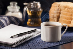Morning work. Morning a cup of coffee and a notepad stock photography