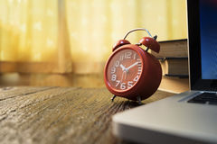 Morning working desktop. Vintage red o'clock , computer laptop and books on wooden table Royalty Free Stock Photo