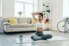 Morning workout. Beautiful young woman in sports clothing practicing yoga while spending time at home royalty free stock photos