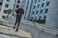 Morning workout. Full length of young african man in sportswear running against modern city buildings. Sport concept. Health concept. Lifestyle royalty free stock photos