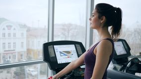 Morning workouts, happy girl on treadmill drinks mineral water from plastic bottle in gym. Against of large panoramic window stock video footage