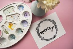 `Morning` written in calligraphy style with hand drawn floral wreath with bouquet of white chrysanthemums on a pink background. To. Morning written in Royalty Free Stock Photography