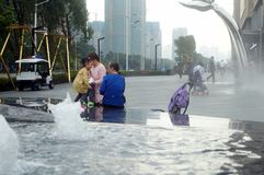Shenzhen, China: adults and children play around the fountain in the shopping mall Stock Photo