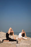 Morning yoga. Beautiful young women practicing yoga on the beach on the rocks. Kapotasana Royalty Free Stock Photos