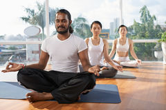 Morning yoga. People meditating in lotus position in yoga studio together Stock Images