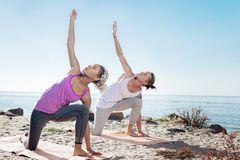 Man and woman doing morning yoga exercises together near the river stock photo