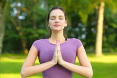 Morning yoga. Young woman does morning yoga in fresh green nature Stock Photography