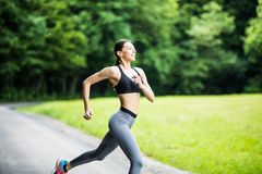 Morning of young fitness woman running outdoors in the park royalty free stock images