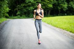 Morning of young fitness woman running outdoors in the park royalty free stock image