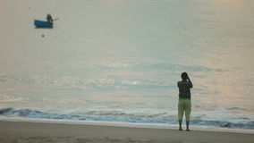 Morning. Young woman taking photograph by cellphone on sea beach stock video