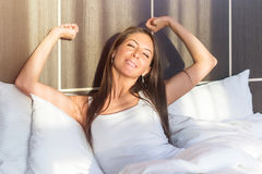 Morning Young woman waking up stretching her arms lying in bed. Royalty Free Stock Image