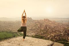 Morning zen-like landscape on sunrise in Hampi. Woman meditate, balancing, doing yoga while traveling in India. Morning zen-like landscape on sunrise in Hampi Stock Photography