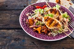 Moroccan barbecue chicken skewer dish with quinoa. A healthy, gourmet Moroccan barbecue chicken skewer dish and utensils with quinoa, mushrooms, chilli and flat Royalty Free Stock Image