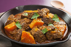 Moroccan Beef Tagine. Moroccan tagine or stew of beef with sweet potato, in a cast iron pan Royalty Free Stock Images