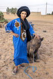 A Moroccan boy stands with a camel at Merzouga, which lies on the edge of Erg Chebbi in Morocco. Royalty Free Stock Photo