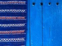 Moroccan carpet on a blue door in chefchaouen  the blue city in morocco Stock Photo