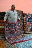 In a moroccan carpet store. Marrakesh, Morocco - March 12, 2014: Oriental berber rugs in a carpet store in Morocco. The seller shows a carpet to buyers Stock Photo