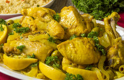 Moroccan chicken. Platter full of Moroccan chicken with lemons and olives served with couscous royalty free stock images