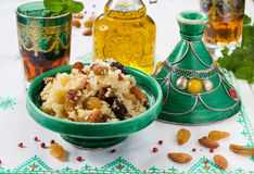 Moroccan couscous with dried fruit and nuts in tagíne. Sweet dessert Moroccan couscous with raisins, dates, dried apricots and nuts in a green tagíne Royalty Free Stock Photography