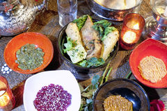 Moroccan cuisine. Different moroccan dishes with candles on carved wooden table Royalty Free Stock Photos