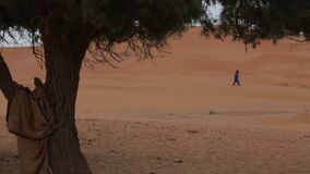 The waiting man in the desert. Moroccan desert. Moroccan man. The waiting man in the desert stock footage