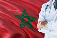 Moroccan Doctor standing with stethoscope on Morocco flag background. National healthcare system concept, medical theme royalty free stock photography
