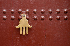 Moroccan Door. An old knocker in the shape of a hand on a door of a traditional Moroccan house in Marrakech, Morocco Royalty Free Stock Photos
