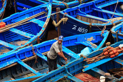 Moroccan Fisherman and blue fishing boats Royalty Free Stock Photos