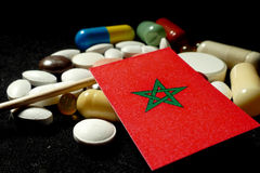 Moroccan flag with lot of medical pills isolated on black background Stock Photos