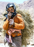 A Moroccan girl carrying a load of hay in the Todra Gorge at Tinerhir in Morocco. Stock Images