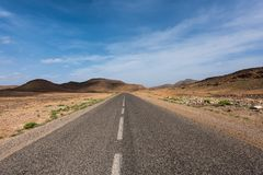 Moroccan highway featuring a rocky desert landscape on a road trip. From Marrakesh to Merzouga royalty free stock image