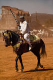 Moroccan horseman with gun. Moroccan horseman in traditional clothes with gun at Fantasia folk celebration, crowd in background Stock Image