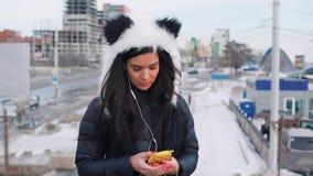 Moroccan kvinna för härligt lockigt långt brunetthår som använder den smarta telefonen i staden arkivfilmer