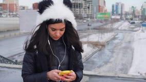 Moroccan kvinna för härligt lockigt långt brunetthår som använder den smarta telefonen i staden lager videofilmer