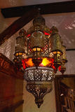 Moroccan lantern lamp illuminating patterns of light on the wall Royalty Free Stock Photo