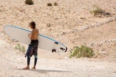 Moroccan man surfer on the beach of Sidi Kaouki, Morocco Stock Photo