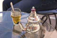 Moroccan mint tea. A glass of Moroccan mint tea with a silver kettle Stock Photos