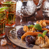 Moroccan mint tea in the traditional glasses with sweets. Stock Photo