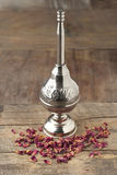Moroccan rose water sprinkler and petals. On wooden table royalty free stock photo