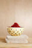 Moroccan saffron treads in bowl, on wood Stock Photo