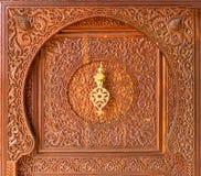 Moroccan style door knocker. On a wooden door Royalty Free Stock Image