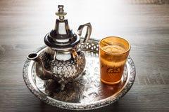 Moroccan tea pot and glass. Close up of a moroccan tea pot and glass on a wooden table Royalty Free Stock Photos
