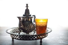 Moroccan tea pot and glass. Close up of a moroccan tea pot and glass on a wooden table Royalty Free Stock Photography
