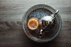 Moroccan traditional tea. Close up of moroccan traditional tea pot and glass on a silver plate Stock Photo
