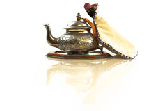 Moroccan traditional tea pot from the front. Vintage look tea pot on a mirror. White background, isolated with a slight reflection in front Stock Photos